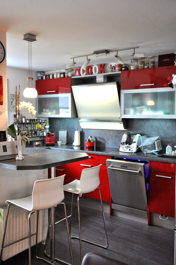 Rote Küche mit dunkler Arbeitsplatte und Nischenrückwand
